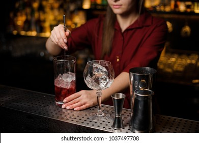 Professional bartender girl stiring a light red cocktail in the glass with ice at the steel bar counter