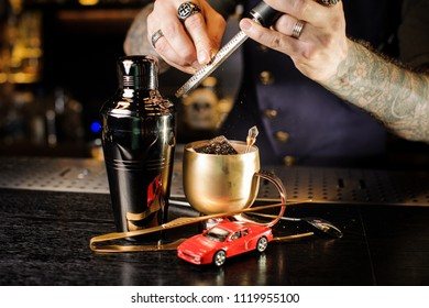 Professional bartender grating nutmeg to the cocktail in the copper cup on the bar counter