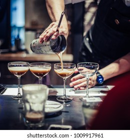 Professional bartender making cocktails in coffee shop, square image