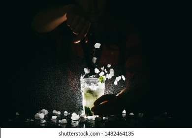 Professional bartender making Mojito cocktail and splashing it out