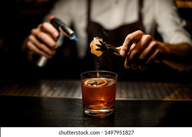 Professional bartender melting caramel with a burner above the cocktail glass with a lemon slice in the dark on the bar counter