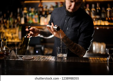 Professional bartender pouring an alcoholic drink making a cocktail from the steel jigger to the glass on the bar counter