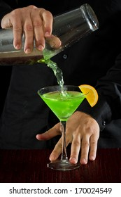 professional bartender pouring a green cocktail in to a martini glass with an orange slice garnish