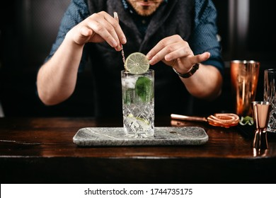 Professional bartender pouring and preparing gin and tonic with lime at bar counter. Details of mixology