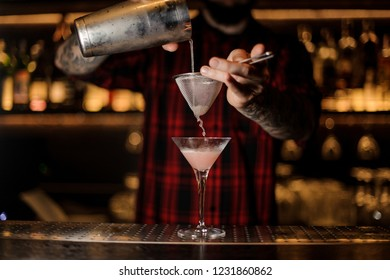 Professional bartender pourring a Cosmopolitan from a shaker through the sieve to a glass on the bar counter on the blurred background