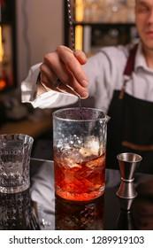 Professional bartender prepairing orange cocktail