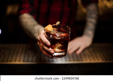 Professional bartender serving a delicious Godfather cocktail decorated with orange zest on the bar counter on the blurred background