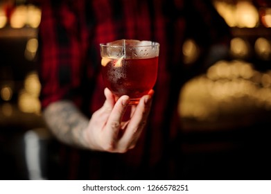 Professional bartender serving a glass of a Vieux Carre cocktail with big ice cube and orange zest on the steel bar counter on the blurred background