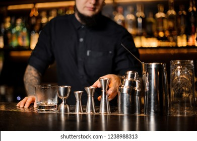 Professional bartender standing on the bar on the foreground of equipment such as jiggers, shakers and strainers