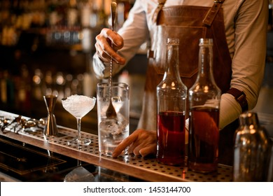 Professional bartender stirring an alcoholic drink with ice in the measuring glass cup near the bottles on the bar counter in the dark blurred background