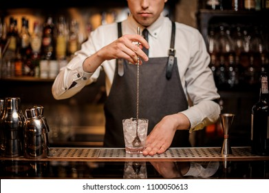 Professional bartender stirring ice in the ornate glass on the bar counter on the blurred background