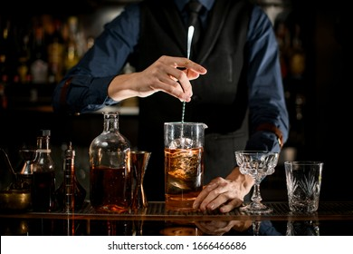 Professional bartender stirs cold cocktail with spoon. Several bottles of alcoholic drinks and glasses standing on the bar counter.
