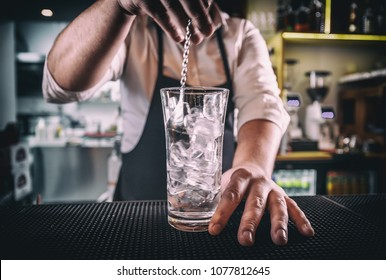 Professional bartender at work in bar mixing ice with vodka in glass for drink