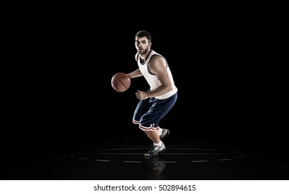 Professional basketball player holding ball on black background