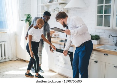 Professional bearded chubby man in formal outfit with clipboard inspecting oven together with attentive ethnic couple while standing at modern sunny apartment