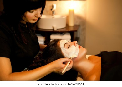Professional beautician applies face mask to a woman in a beauty salon.