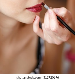Professional beautician artist applying makeup  on young model.