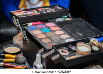 professional beautician with brushes and a variety of shadows and blush of makeup artist