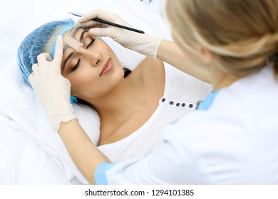 Professional beautician is going to correct eyebrow line at woman face using cosmetic ruler. Permanent brow makeup in beauty salon, closeup.  Cosmetology treatment