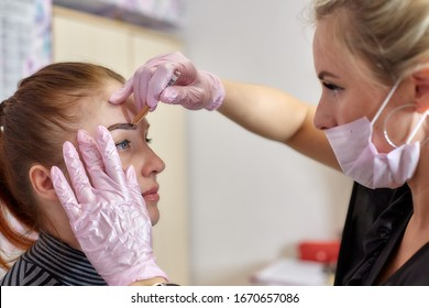 a professional beautician makes a mark on the client's face before eyebrow tattooing, permanent makeup.