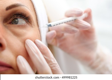 Professional beautician making botox facial injection