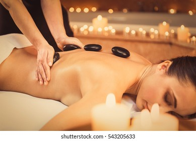 Professional beautician massaging female back by stones