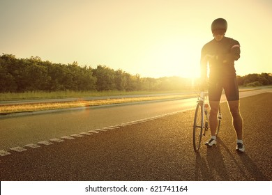 The professional biker standing and holding a cycle while looking the time.