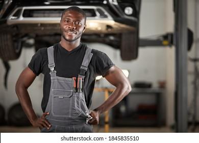 un mécanicien de l'auto noir professionnel regardant la caméra, un beau gars noir en uniforme est enthousiaste à l'idée de réparer une voiture. voiture en arrière-plan