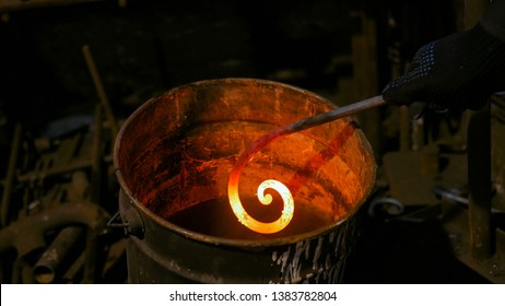 Professional blacksmith working with metal - quenching hot iron part of forged gate in water at forge, workshop. Handmade, craftsmanship and blacksmithing concept