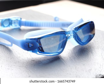 Professional Blue glasses for swimming on a gray background