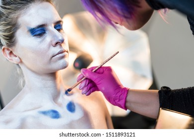 Professional body art artist at work. Painting oriental patterns on the skin of a woman. Makes a body art. Body painting in process. Young female nude body art painter