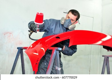 Professional body shop worker painting red ca bumper.