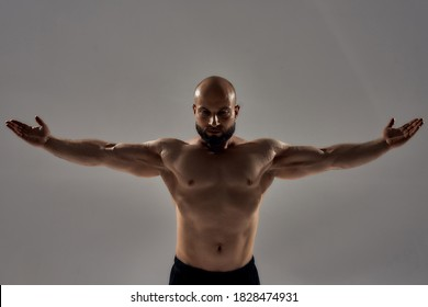 Professional bodybuilder posing. Muscular strong bald man with naked torso standing with outstretched arms isolated over grey background. Sport, bodybuilding, workout concept