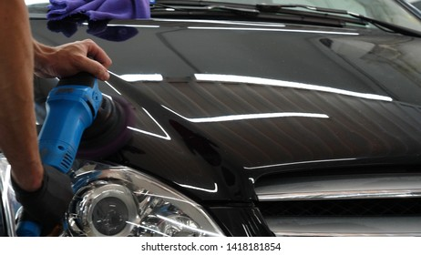 A professional bodywork and headlamp polishing worker will transport the car after painting or preparing for sale. Concept of: Freshen cars, Automotive center, Service, Professional.
