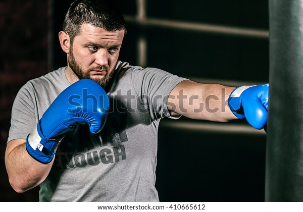 Professional boxer fighting and training in gym in blue boxing gloves. Strong, muscular man training and boxing in fitness gym.