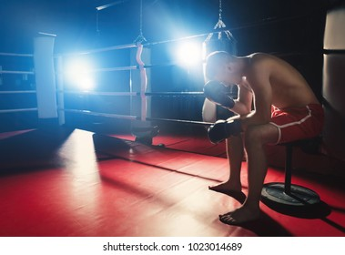 Professional boxer having break during training in ring