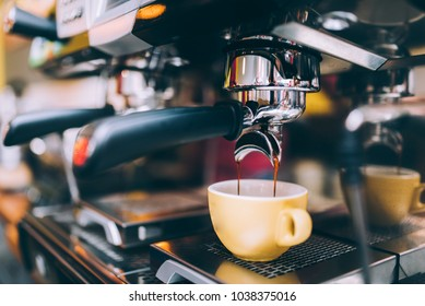 Professional brewing - coffee bar details. Espresso coffee pouring from espresso machine. Barista details in cafe shop