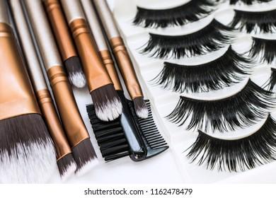 Professional brushes for make-up and set of false eyelashes on a white background