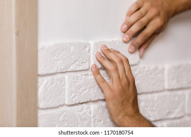 Professional Builder gluing decorative tile on wall. worker mounts decorative brick on wall