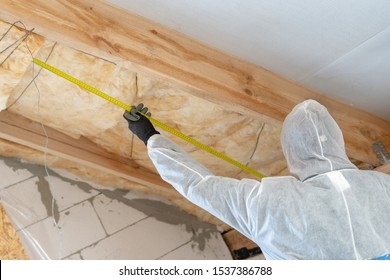 Professional builder man in white protective overall holding measuring tape near material, installing thermal insulation layer with fiberglass wool under the roof