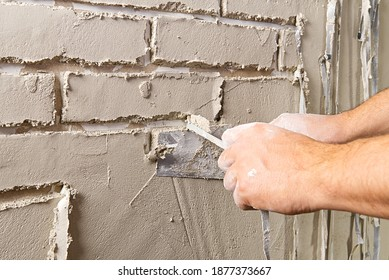 Professional Builder moulding decorative tile on wall from gips plaster . worker removing tape under plaster to imitate decorative brick on wall