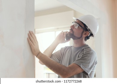 Professional builder with safety helmet having a phone call, home renovation and communication concept