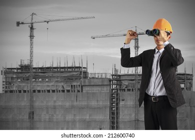 professional builder wearing helmet and hand show up . man see vision forward and success of future on the background of a new high-rise apartment buildings and construction cranes