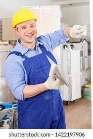 Professional builder working on overhauls indoors, puttying and renovating walls