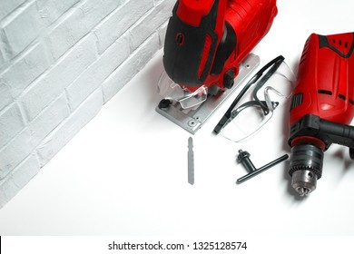Professional building electrical tools for wood and metal. Electric jig saw and drill with safety glasses on a brick wall background