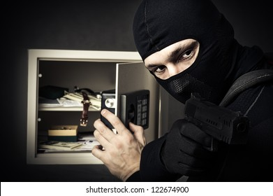 Professional burglar in black mask opened a small safe, holding hand gun and aiming