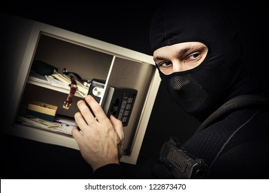 Professional burglar in black ski mask opened a small safe, holding hand gun and aiming