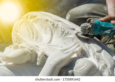 Professional Burmese stone engraver uses a marble grinding machine to carve white marble a Buddha statue