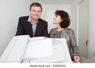 Professional business man and woman standing  in the office a with confident smiles at the success of their partnership