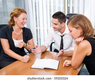 Professional business manager telling about new ideas for their company. His office worker big laughing while sitting at the table in board room.